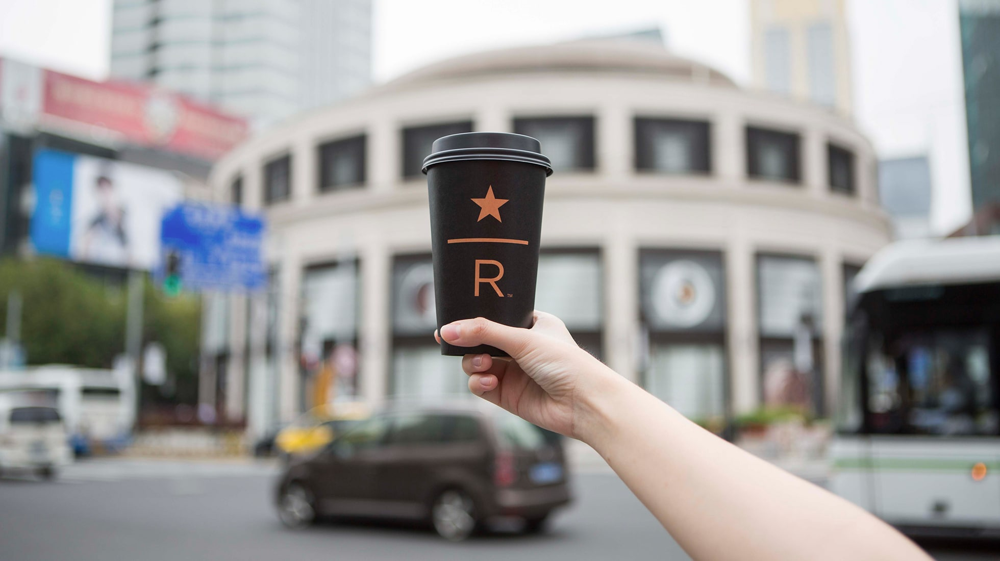 Hand holding black Starbucks Reserve paper cup, in front of a building
