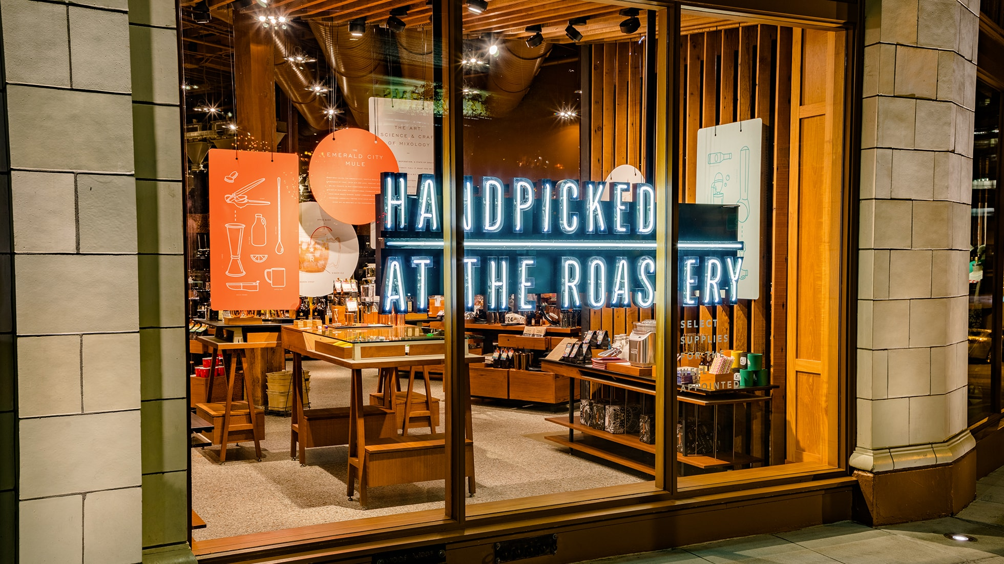 """Storefront with neon sign that reads """"Handpicked at the Roastery"""" with merchandise in the background"""