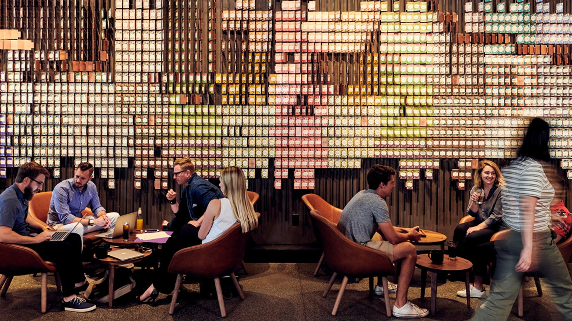Two small groups seated around low tables with Starbucks Reserve card wall installation behind them