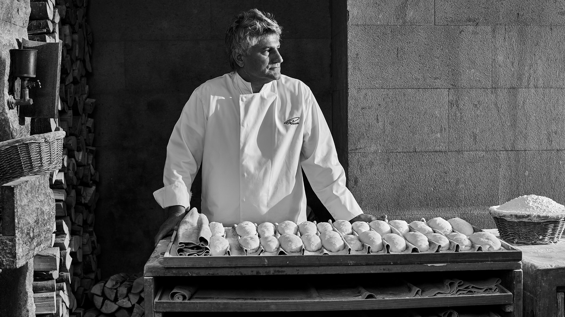Black and white image of man looking into the distance to the right, near a tray of baked goods and a basket of flour