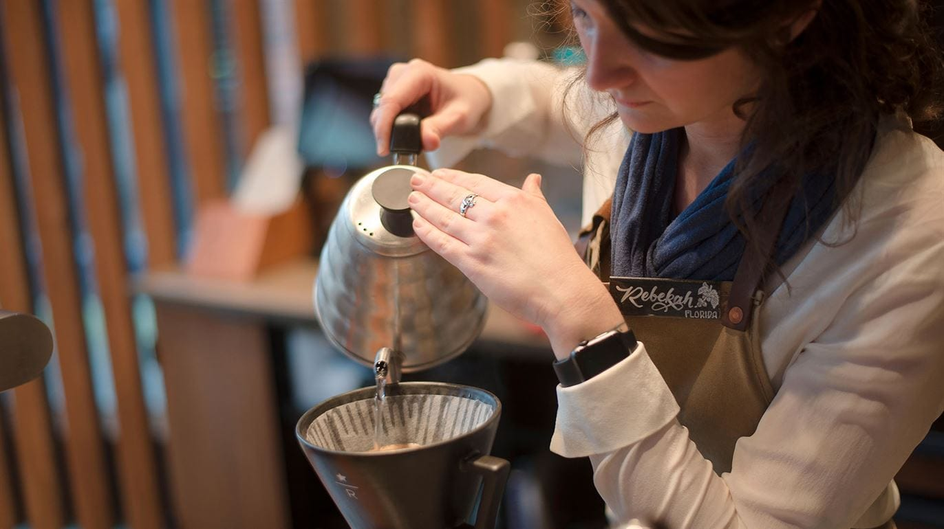 "Woman with nametag ""Rebekah"" pouring water from a gooseneck kettle into a Starbucks Reserve-branded pour over"