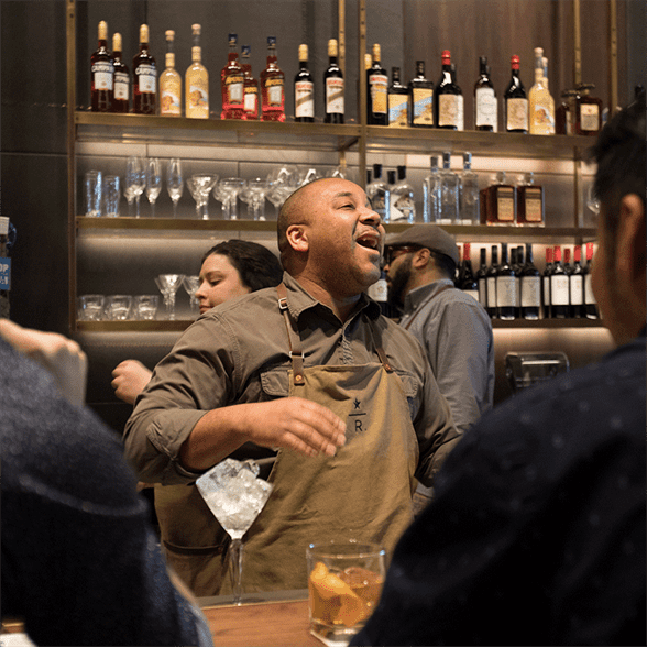 Man in apron laughing among other people in bar setting