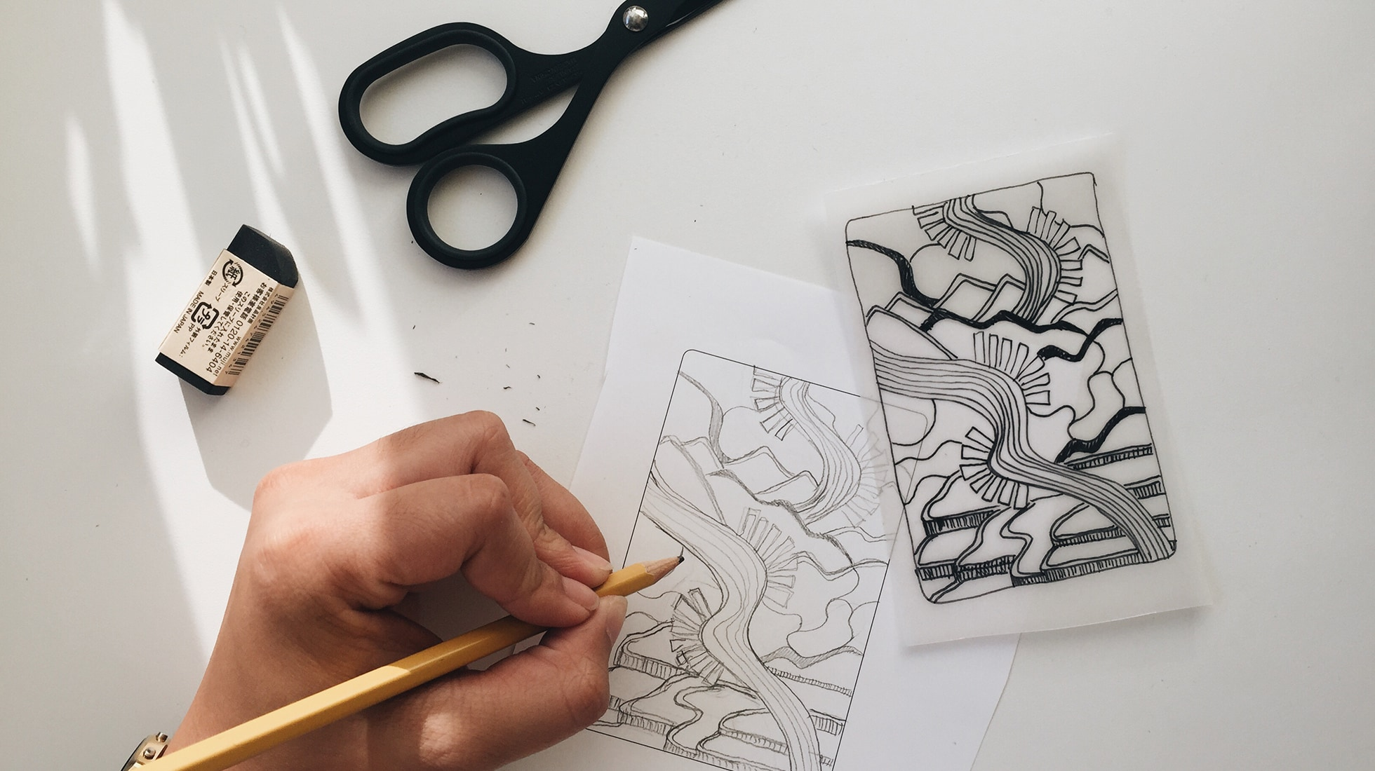 Overhead image of a hand holding a pencil over a pencil drawing, with an eraser, scissors, and an ink drawing of the same pencil drawing on tracing paper