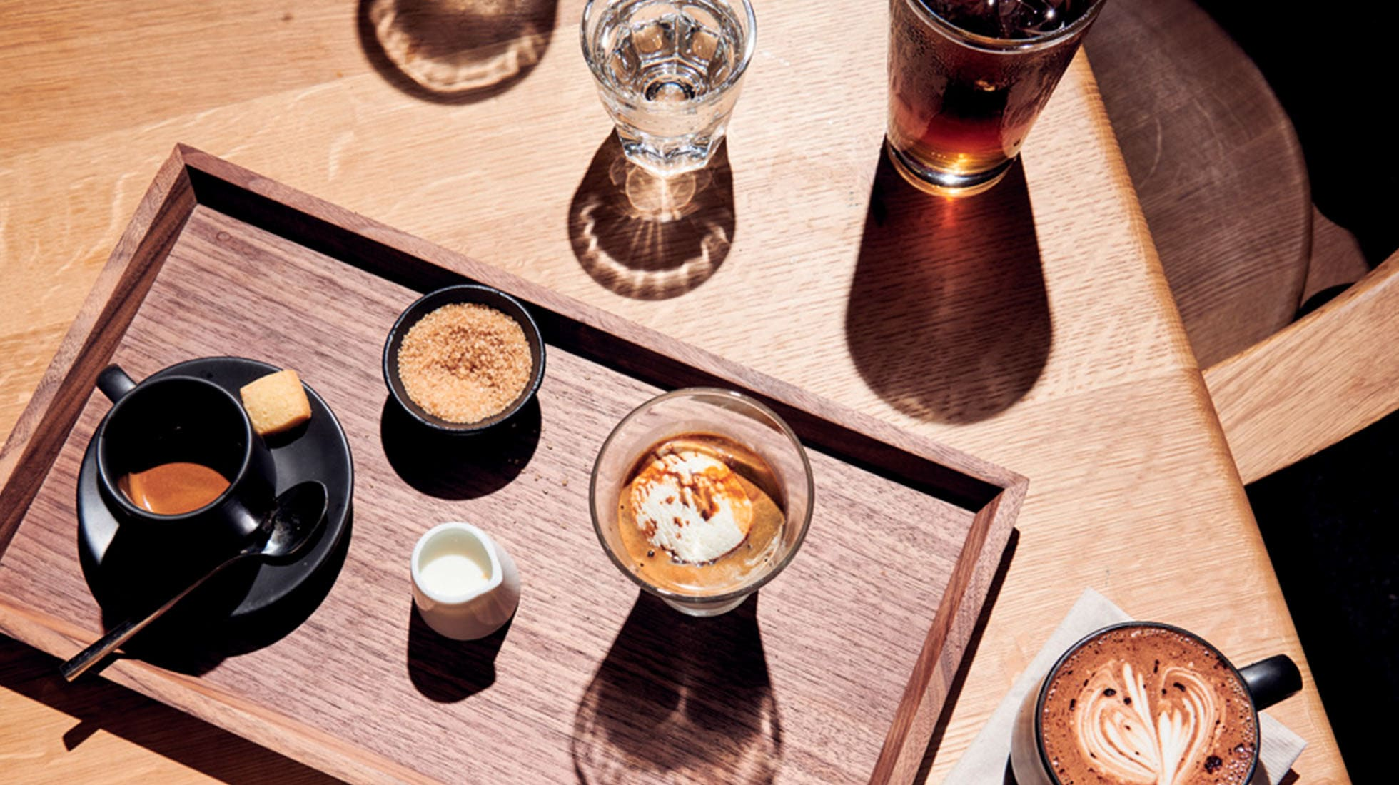 Assorted coffee beverages on a wooden tray and wood table, shot from above