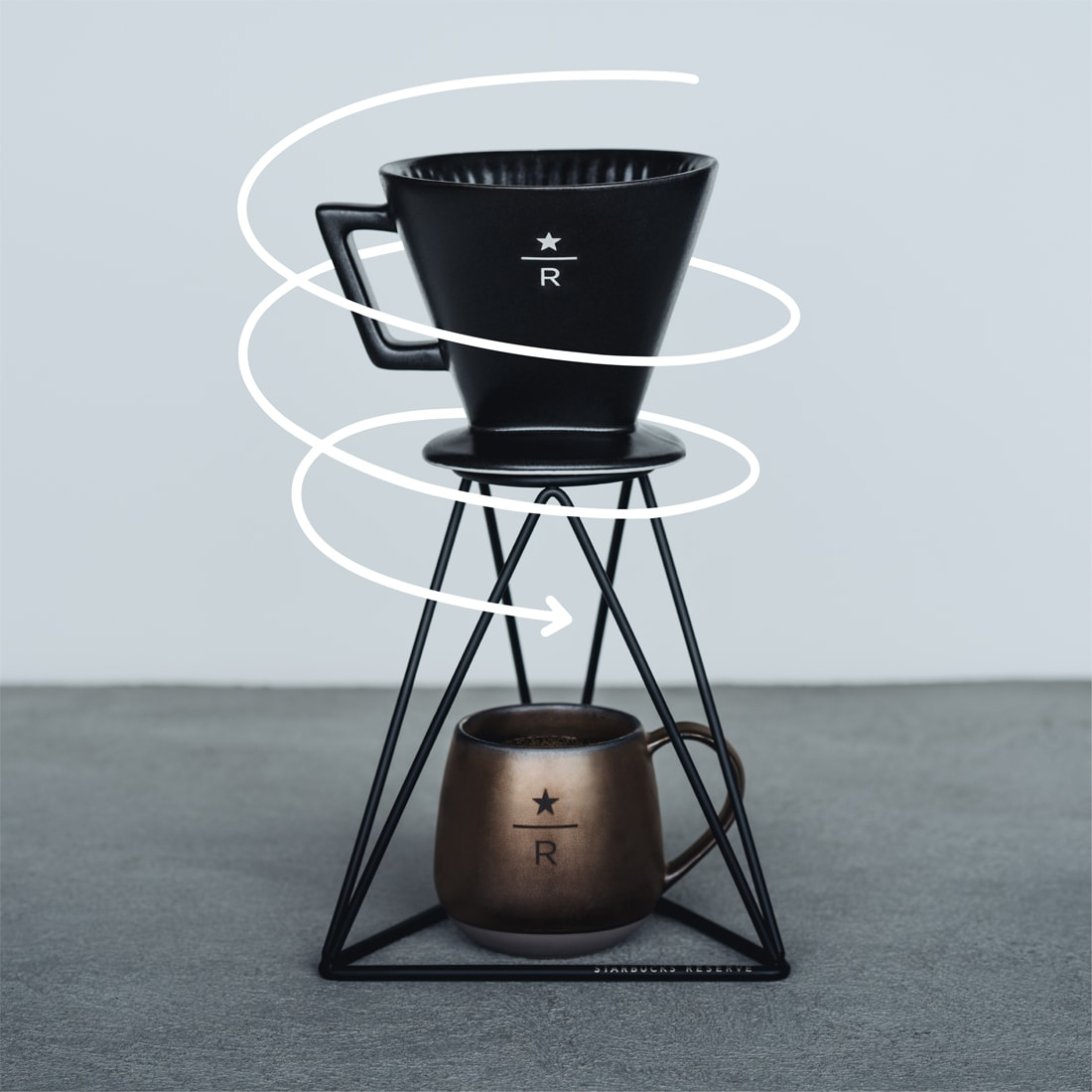 Pour-over brewer with overlaid line illustration of a spiral arrow around the pour-over