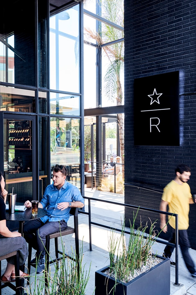 An exterior space with a Starbucks Reserve logo, two people sitting at a table with beverages, and another person walking by