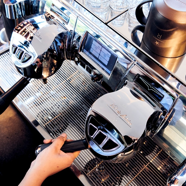 Overhead angled shot of a hand operating an espresso machine