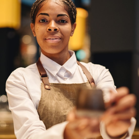 Starbucks Reserve employee holding out a cup, which is blurred