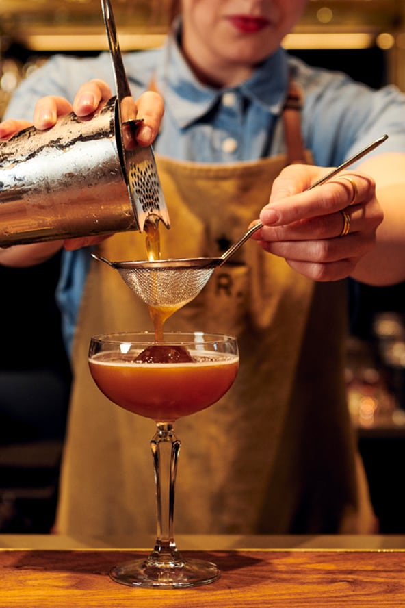 Starbucks Reserve mixologist straining liquid from a shaker into a cocktail glass