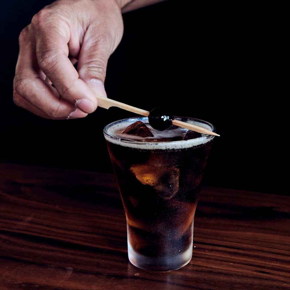 Hand placing a speared cherry on the rim of a cocktail