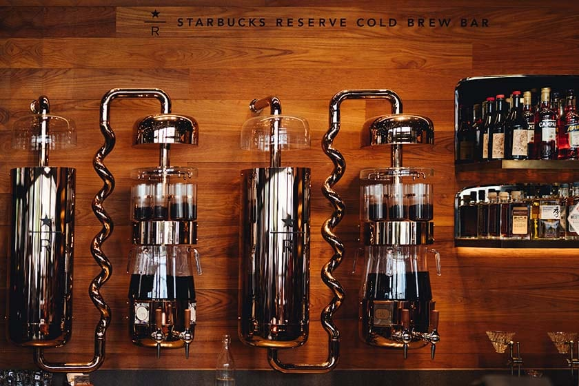 Large copper containers with spiral tubing into glass and copper containers with coffee beans at the top and brewed coffee beneath, next to bottles of alcohol.