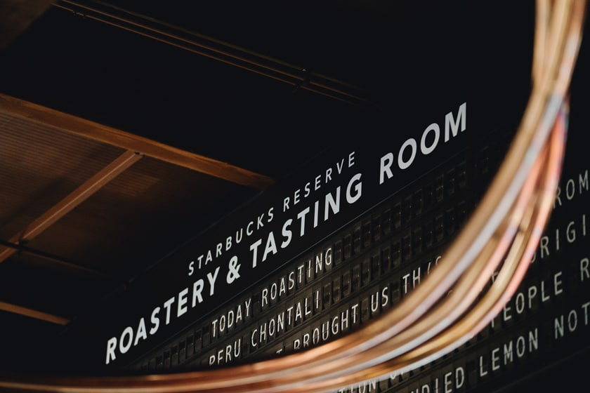 "Split flap (train departure / arrival-style) display for ""Starbucks Reserve Roastery & Tasting Room"" that indicates the types of coffee ""Today Roasting""; out-of-focus copper tubes in the foreground"