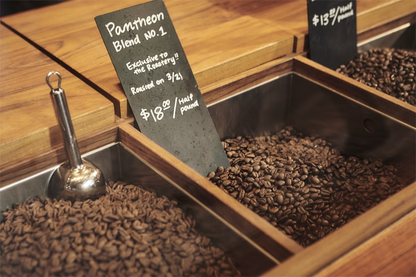 Square containers filled with coffee beans inset into wood counter, scoop and handwritten labels of coffee type and pricing sit in the coffee beans