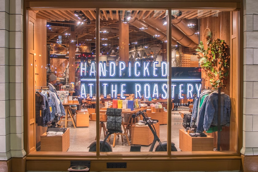 "Storefront with neon signage ""Handpicked at the Roastery"", as well as clothing, a bicycle, and other indistinct items"