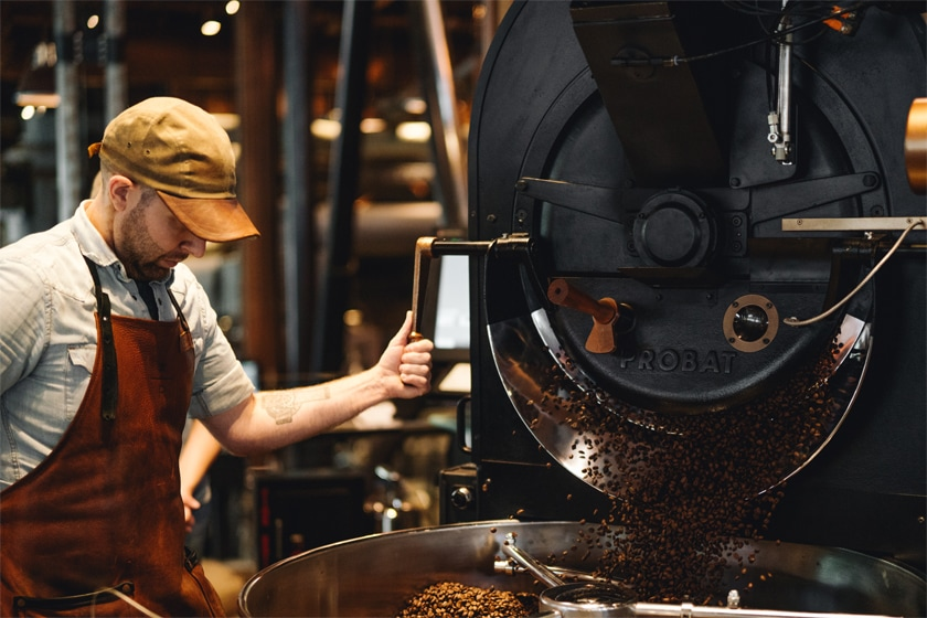 Man wearing brown leather apron operating large roaster; beans pouring out of roasting chamber and into cooling tray