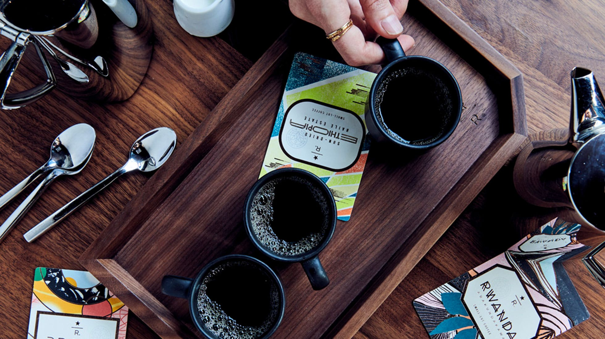 Overhead shot of multiple cups of coffee on a tray with coffee cards, as well as spoons and pots
