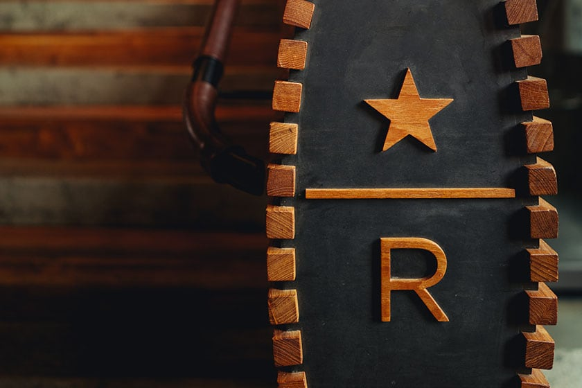 Close-up of wooden railing with carved Starbucks Reserve logo in foreground; steps out of focus in the background
