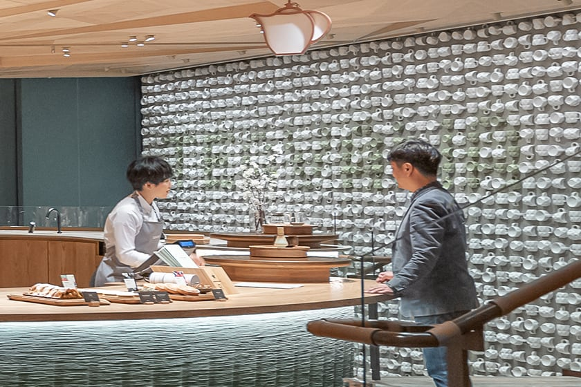 "A rectangular art piece made of 2,300 Teavana tea cups attached to a wall, with ""TEAVANA"" spelled out within, and Teavana barista and customer in foreground"
