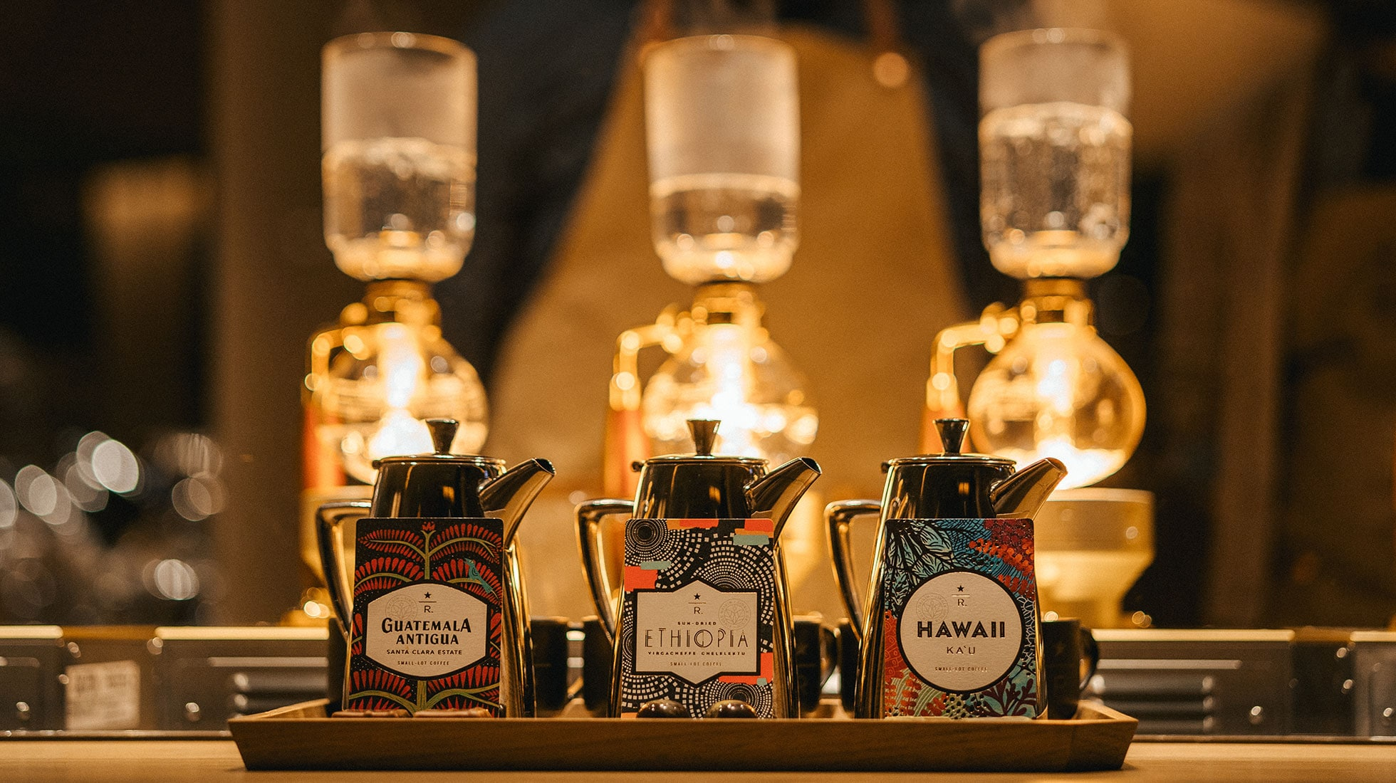 Three carafes of coffee and colorful coffee cards on a wooden tray, with a background including baristas and glowing siphon brewers