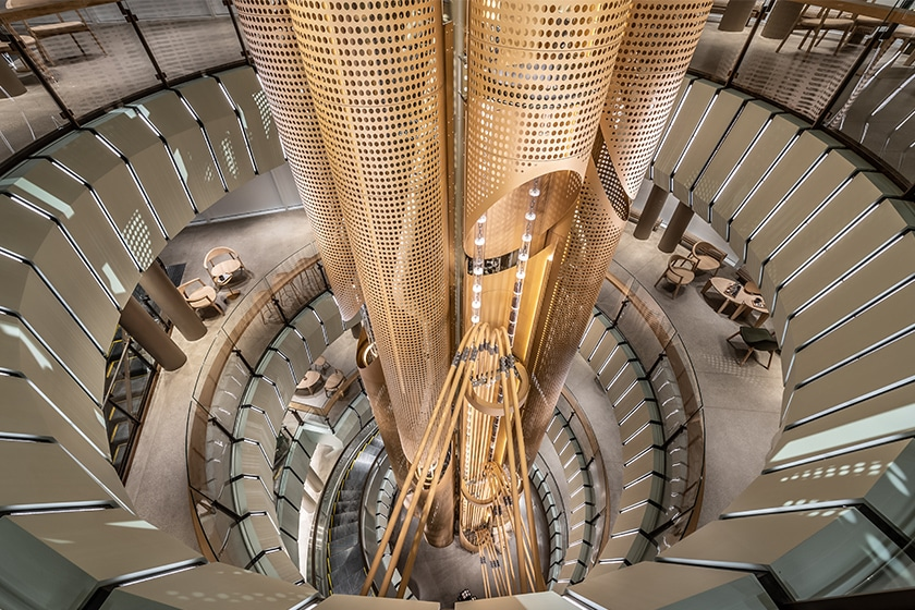 A foreshortened view looking down at the Chicago Roastery metal cask from the fourth floor to the first floor, with both clear and metal tubes transporting coffee, and a spiral escalator and some seating visible on the different floors