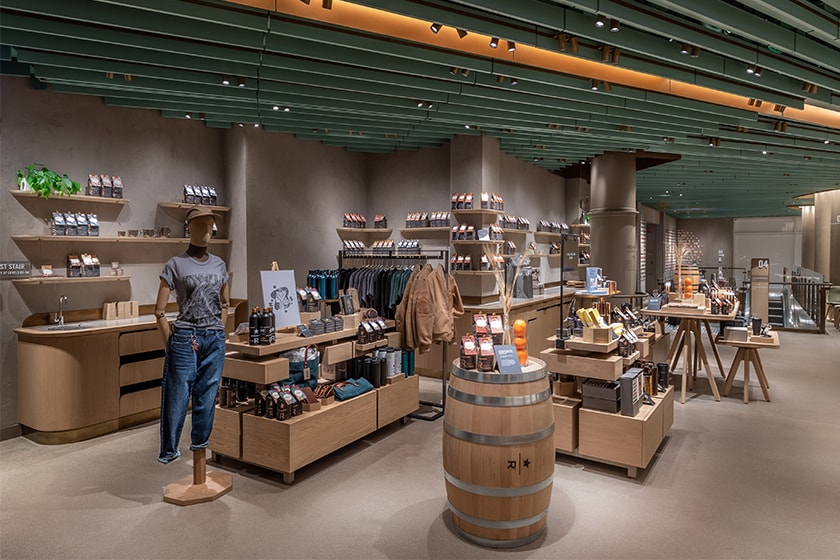 Display tables with a variety of products, including coffee, drinkware, brewing equipment and apparel, plus a mannequin and whiskey barrel in the foreground