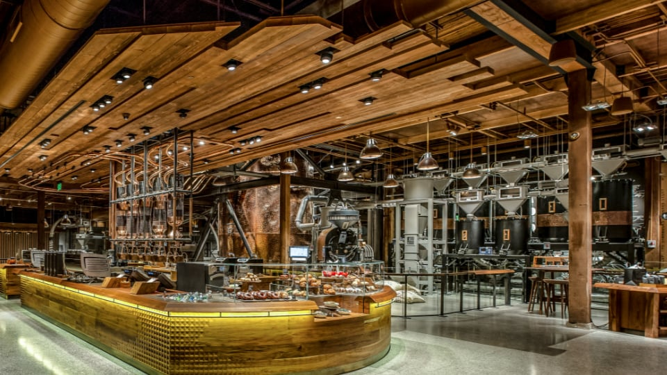 The Main Bar in the Seattle Roastery, with a background including a large roaster, copper cask and storage silos