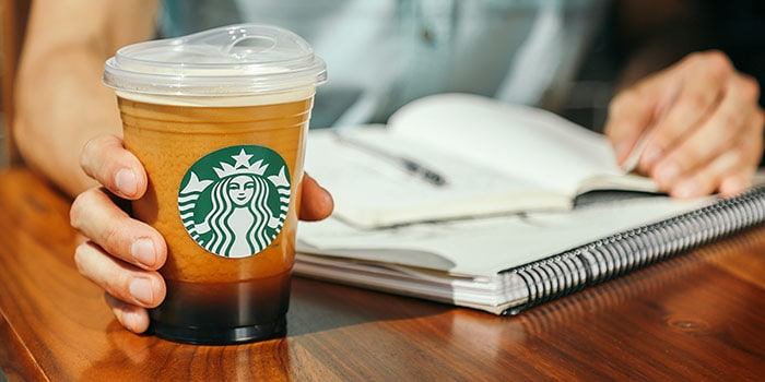 Hand holding Starbucks cold cup without straw