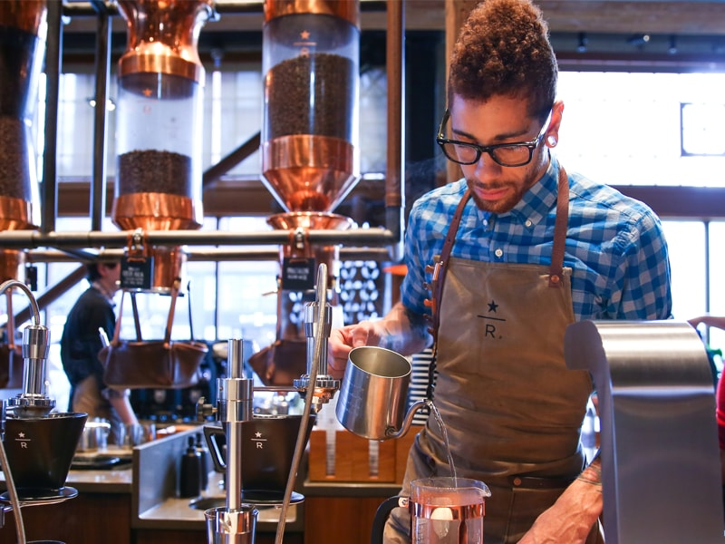 male partner at roastery pouring hot water into french press