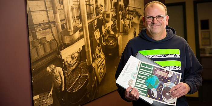 Smiling manufacturing partner with glasses holding magazines