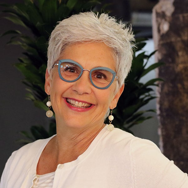 smiling woman with short white hair and blue frame eyeglasses