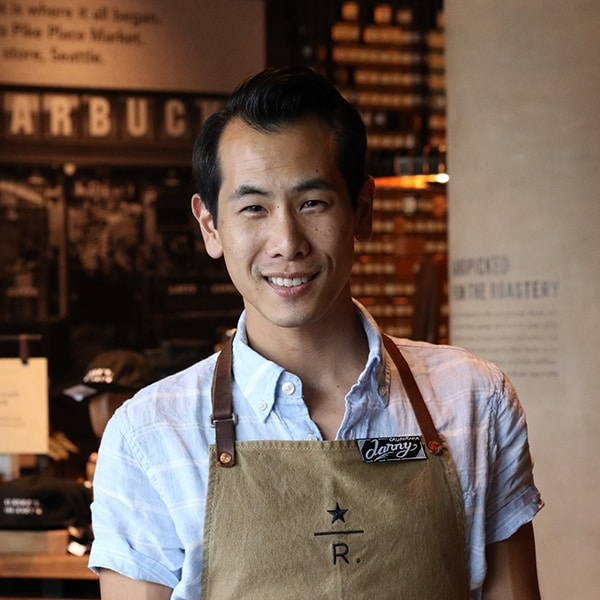 Male employee smiling wearing brown roastery apron