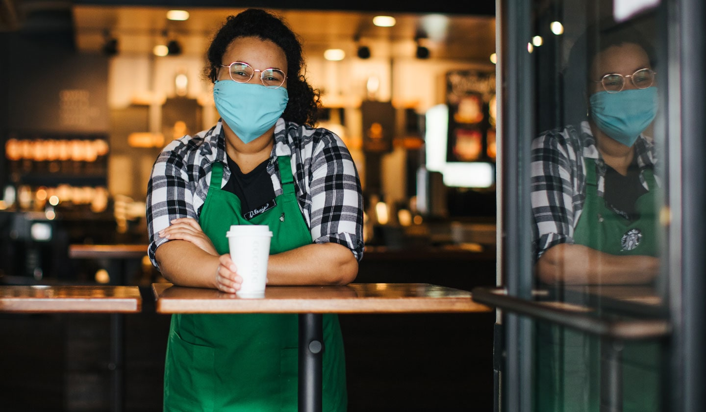 Starbucks barista wearing a facial covering.