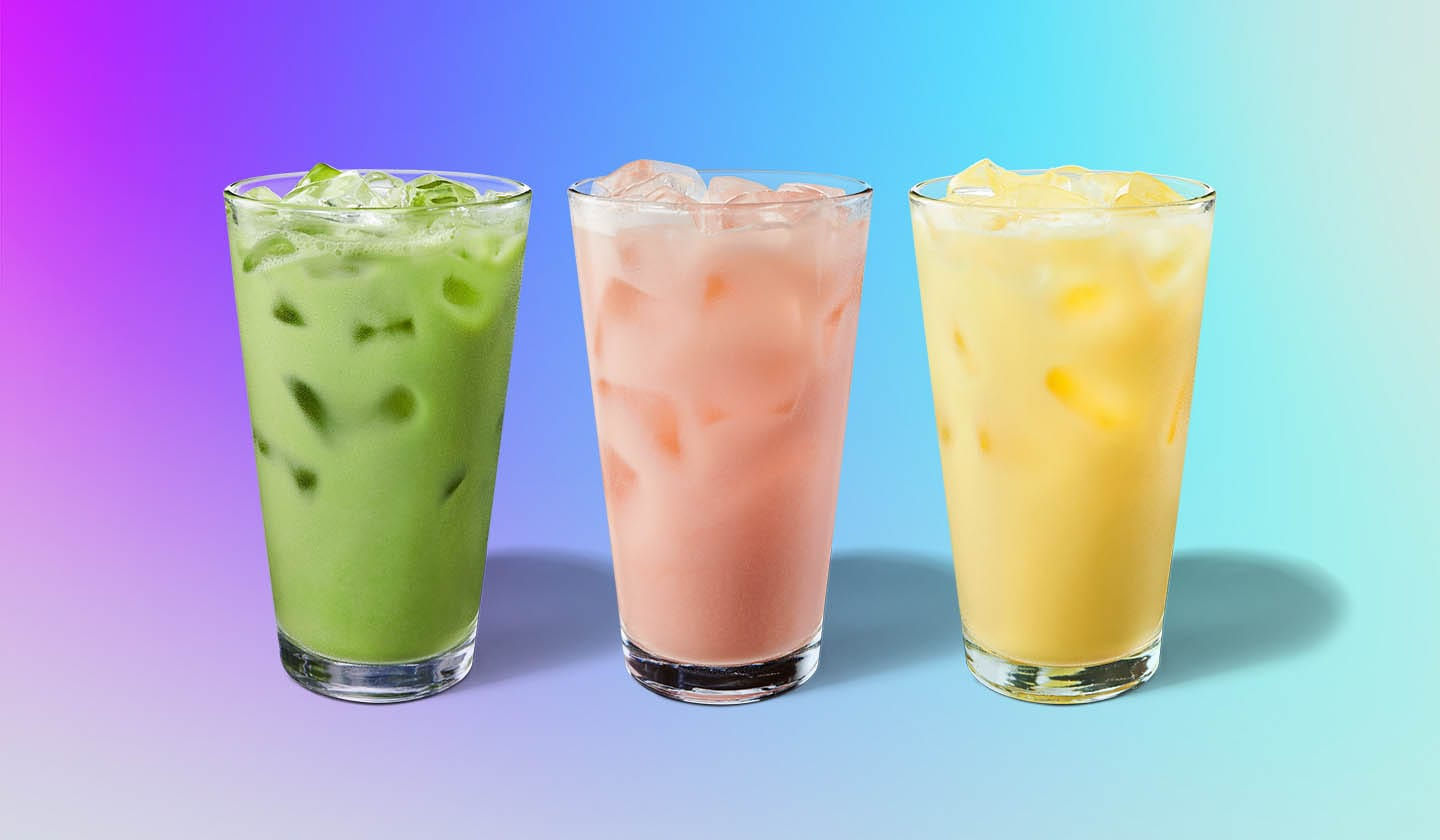 Three colorful iced coconutmilk drinks in clear glasses