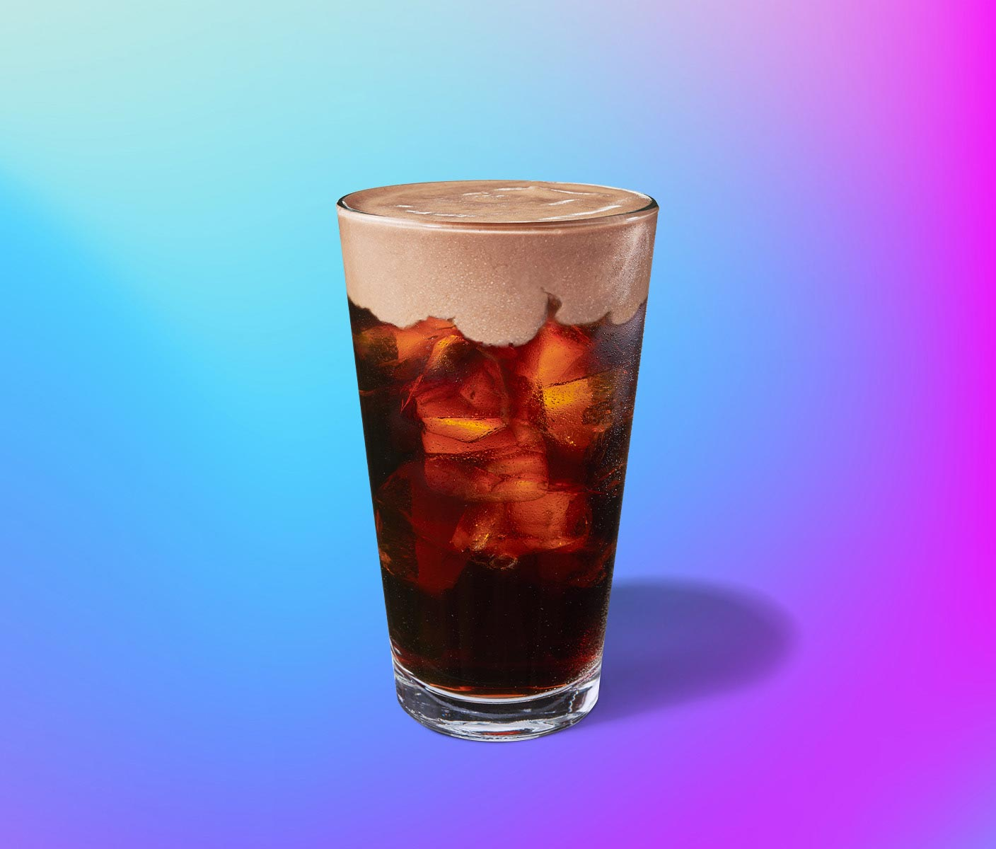 Cold coffee drink with foam topping in a clear glass