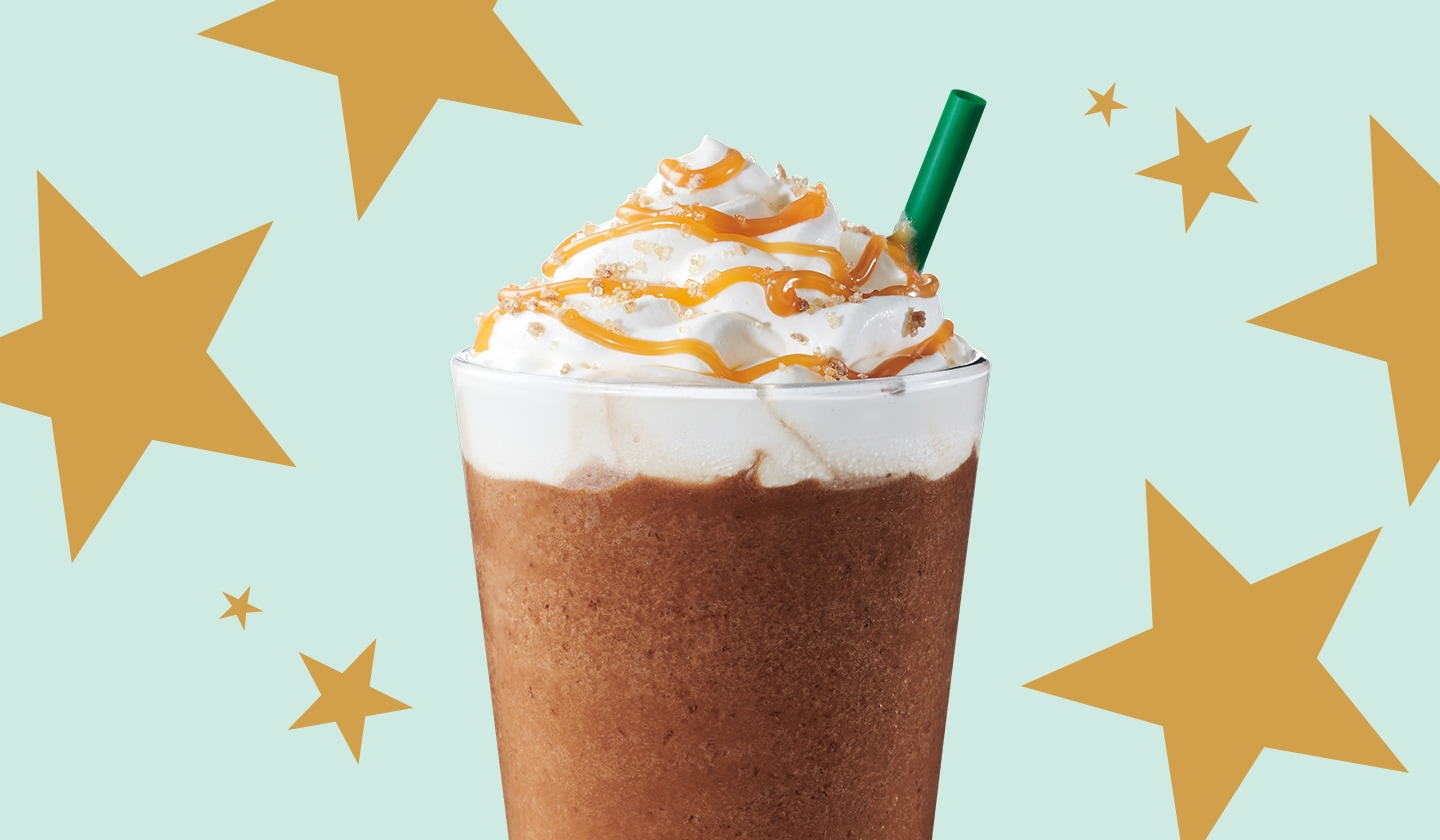 A blended Starbucks beverage topped with whipped cream sits on a pattern of gold stars atop a mint green background.