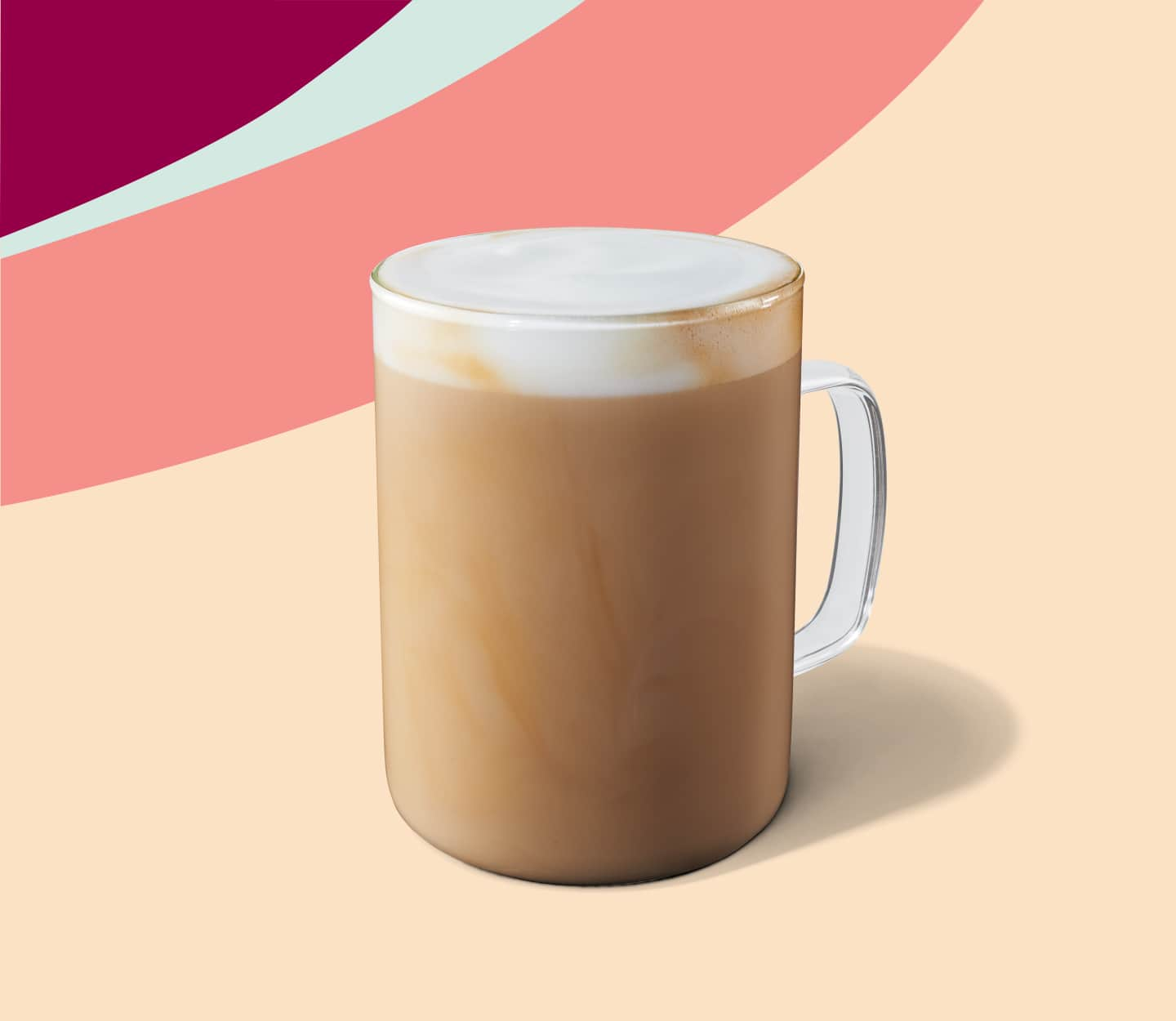 A creamy latte served in a glass mug.