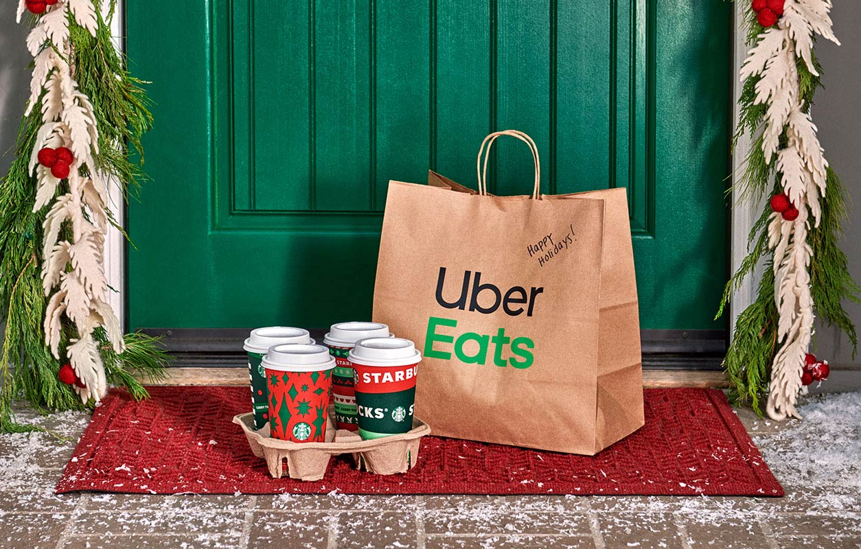 An Uber Eats delivery bag and Starbucks holiday beverages have been delivered to a wintery doorstep.
