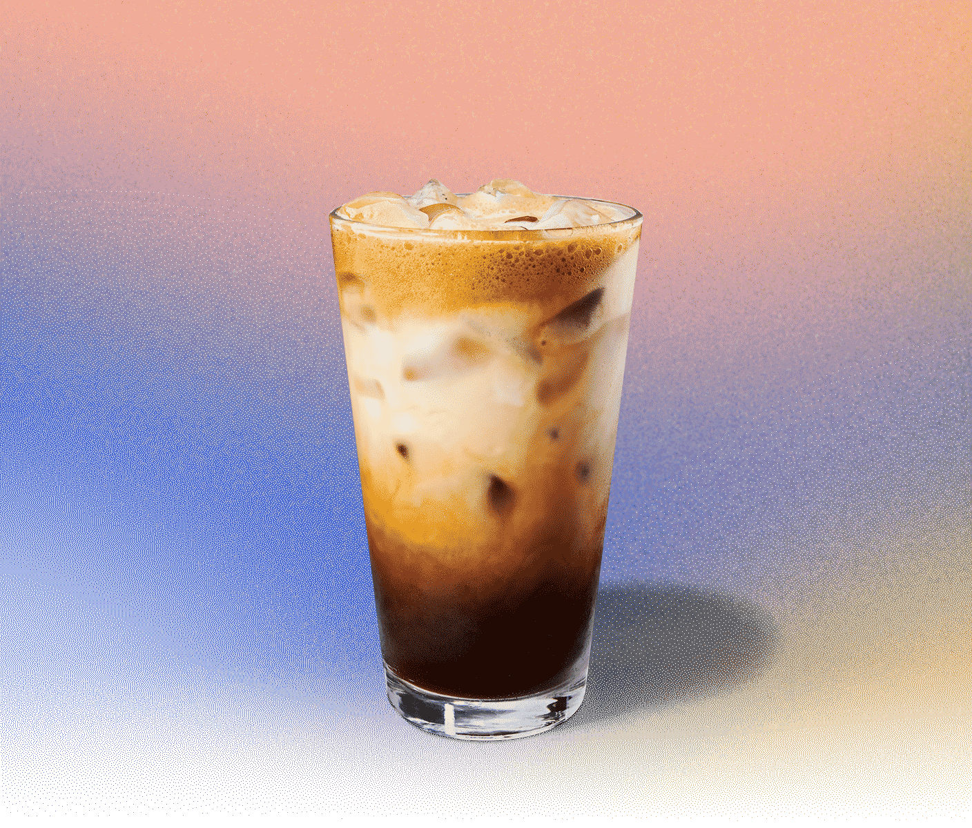 Tall iced espresso drink in a glass with creamy portion near the top