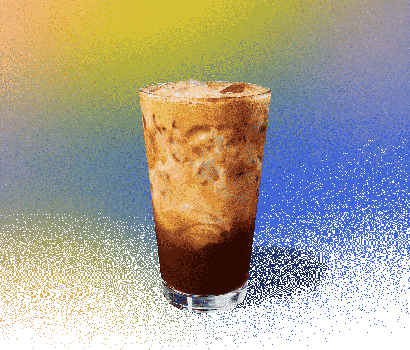 Tall iced espresso drink in a glass with swirls of creaminess throughout