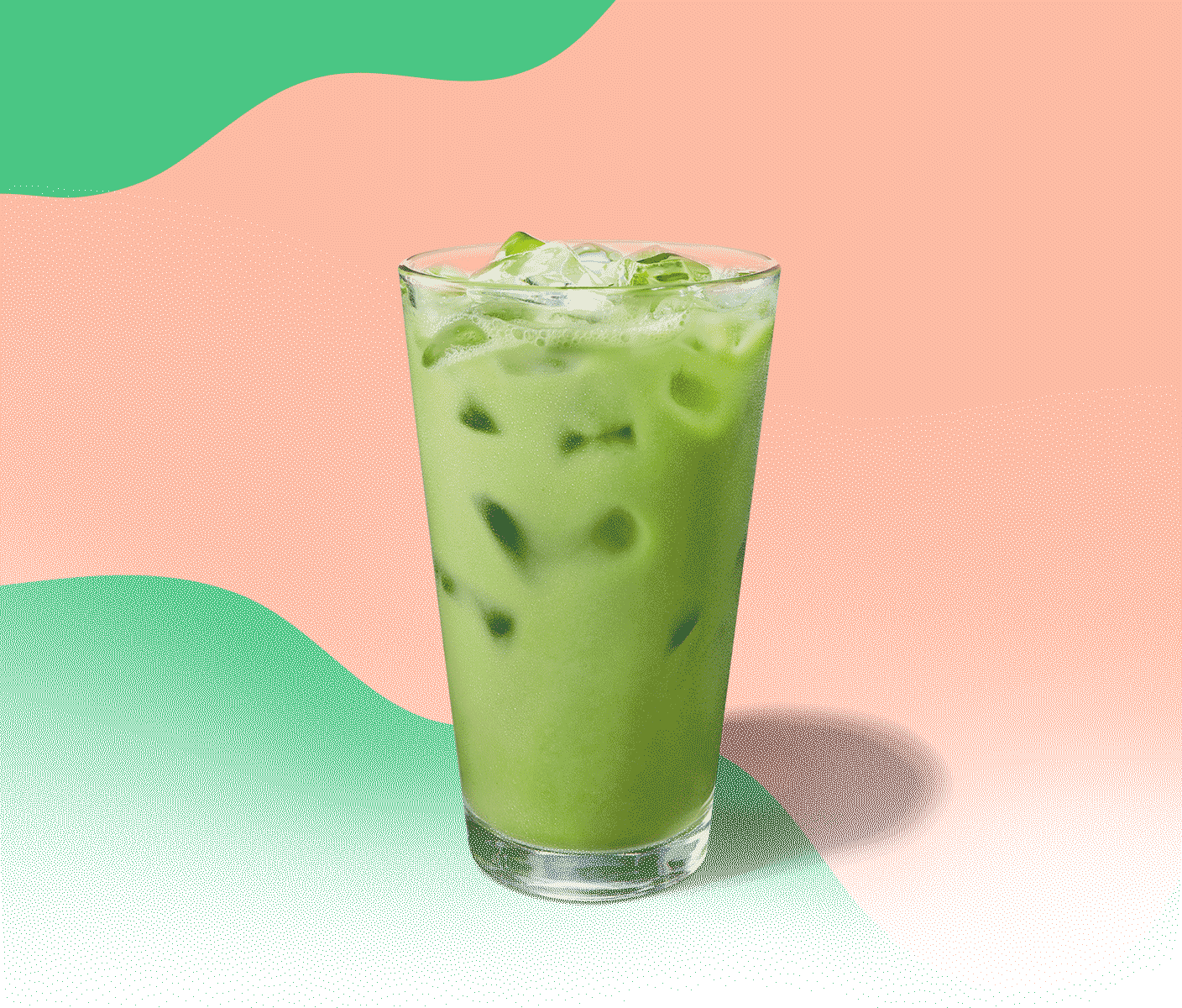 Green iced drink in a tall glass against a colorful background
