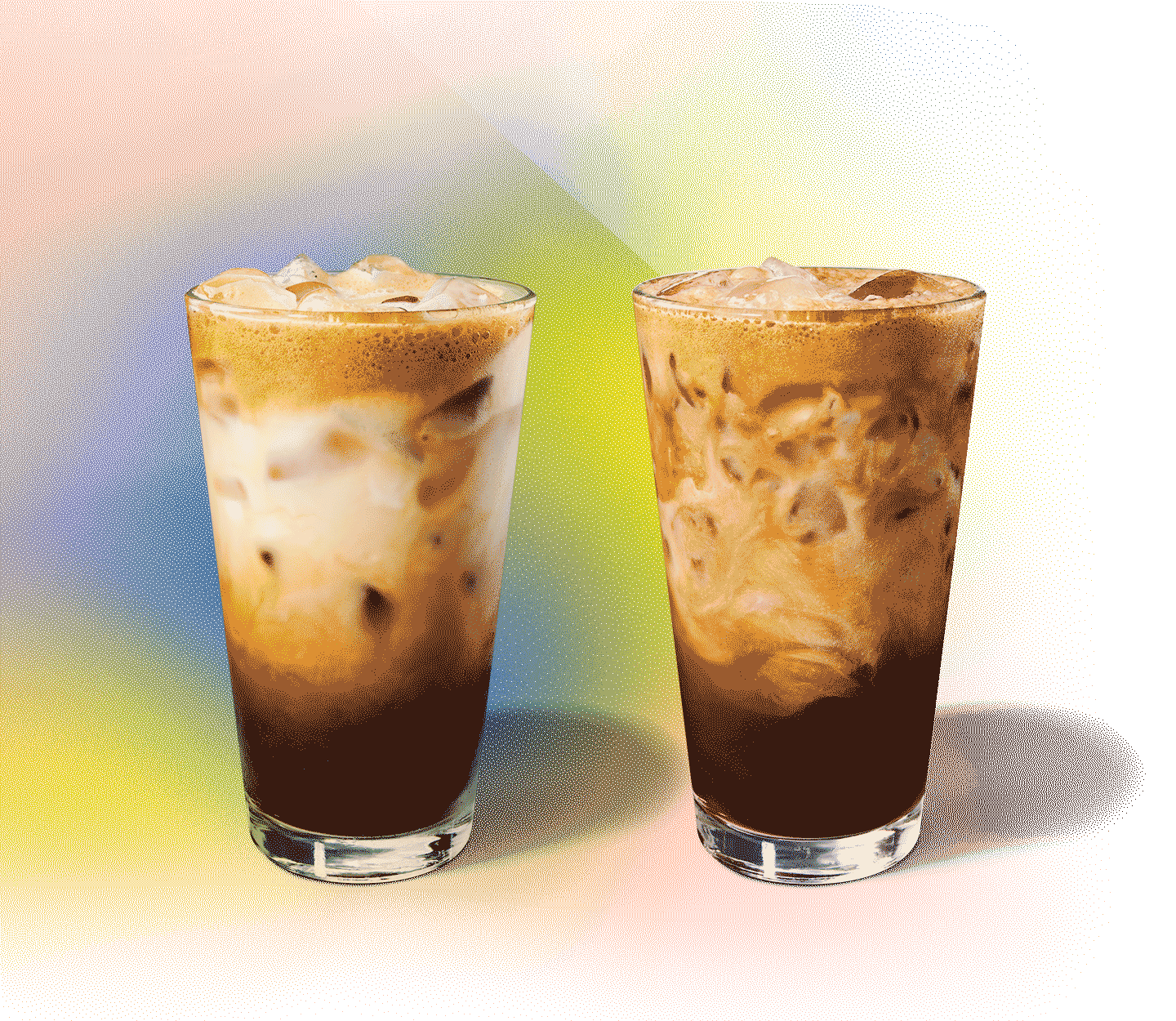 Two iced drinks with creamy swirls sit side by side