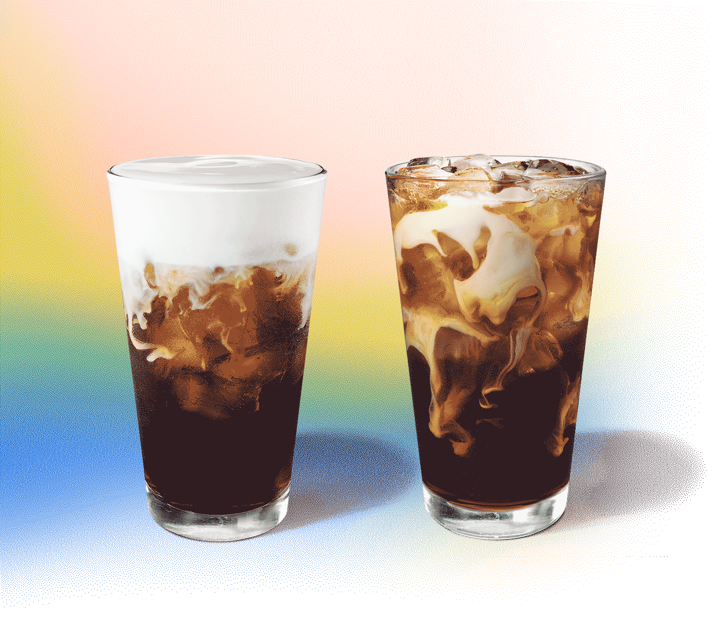 Two coffee and cream drinks in a glass sit next to each other.