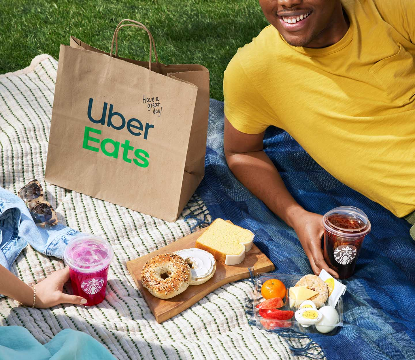 Two friends sit with an Uber Eats delivery bag and assortment of Starbucks coffee and bakery items in an outdoor picnic setting.