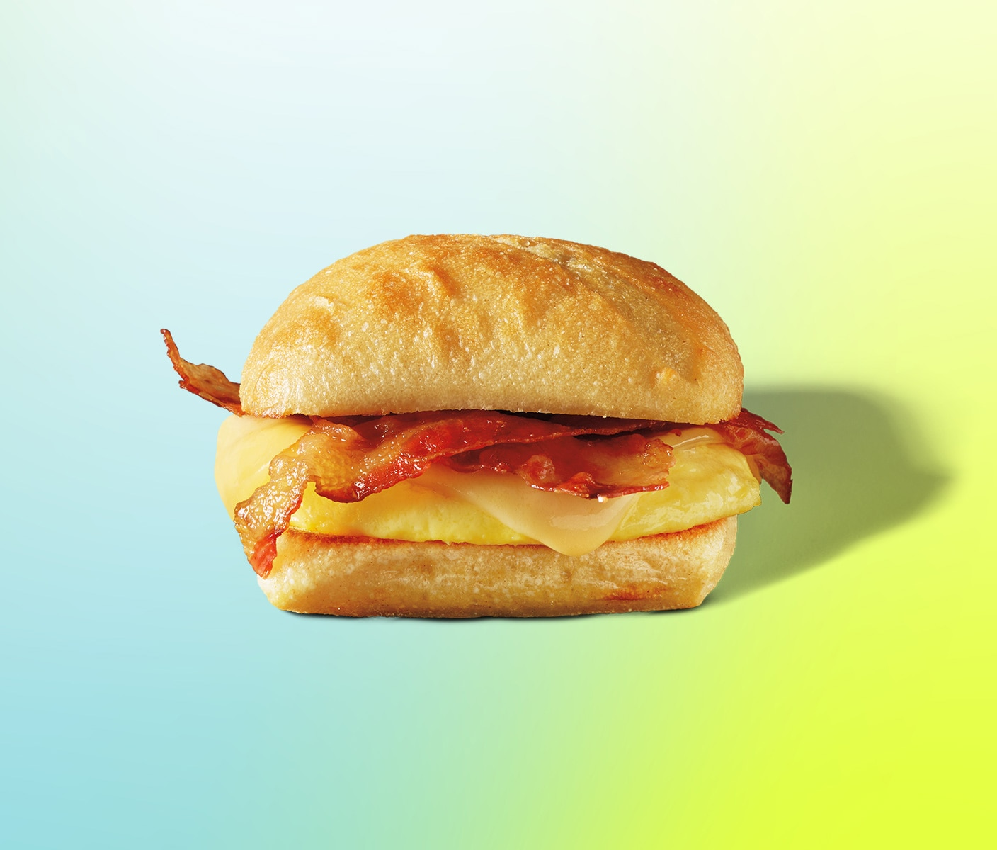 Layered sandwich with bacon strips and melted cheese on an artisan roll.