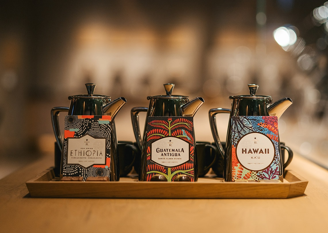 3 beautiful packages of coffee in front of stylish coffee pots.