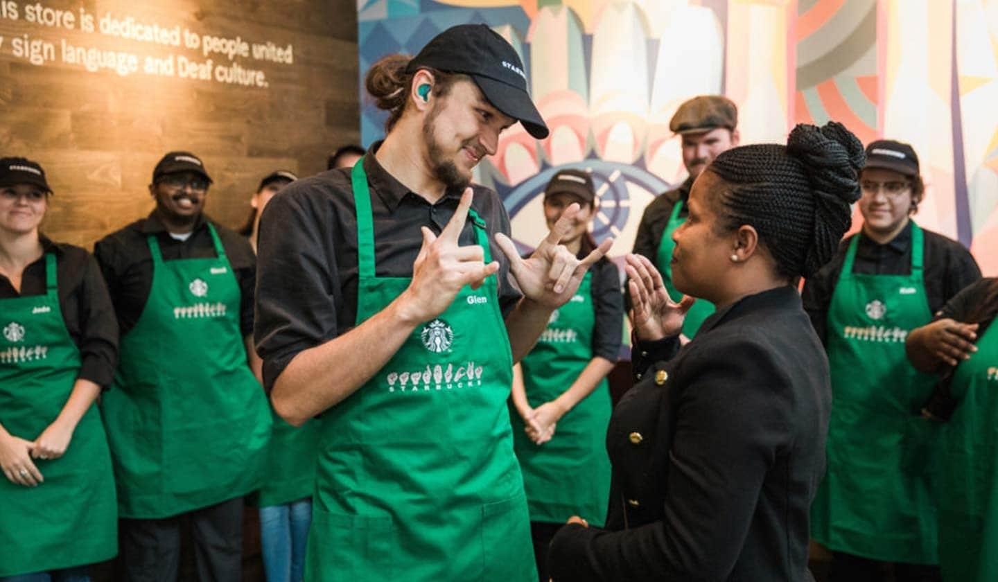 Photo of a man and woman using sign language with each other. They are wearing Starbucks green aprons with sign language signs on them and are surrounded by fellow employees.