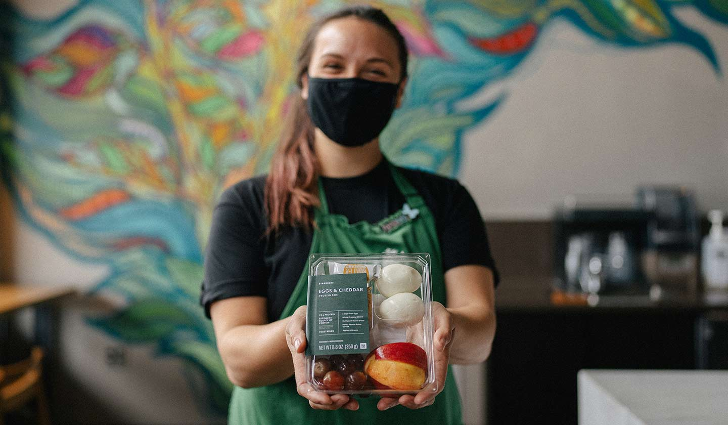 Starbucks barista wearing a green apron and extending an eggs and cheddar protein box.