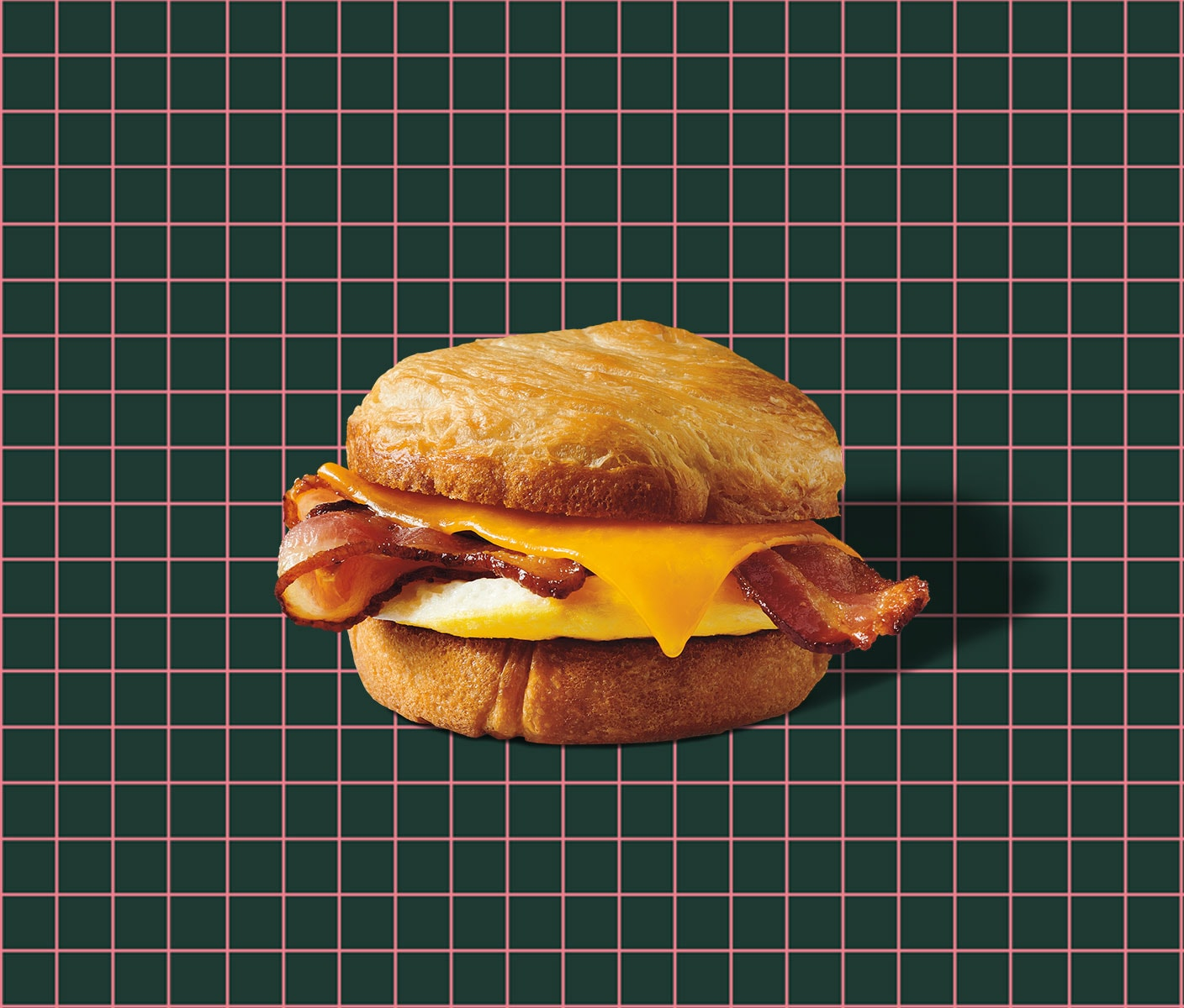 A breakfast sandwich sits atop a grid background.