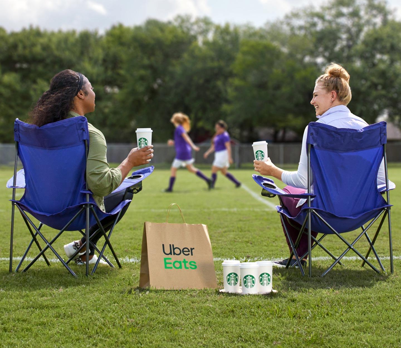 Two women sitting on a soccer field drinking coffee.