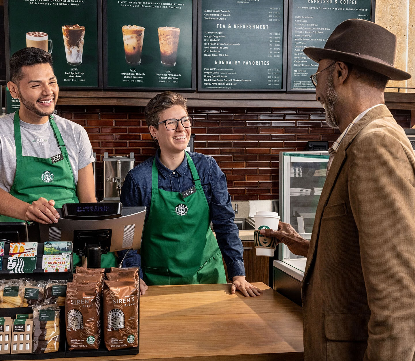 Two smiling baristas serve a Starbucks hot coffee to an older customer.